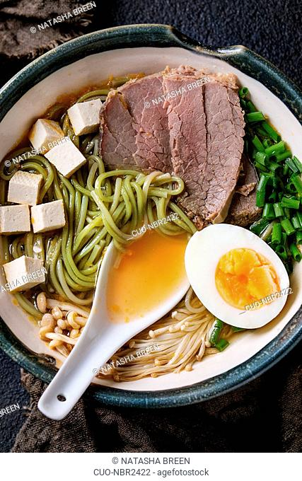 Bowl of asian style soup with green tea soba noodles, beef, egg, mushrooms, spring onion and tofu cheese, served with white spoon on sackcloth over black...