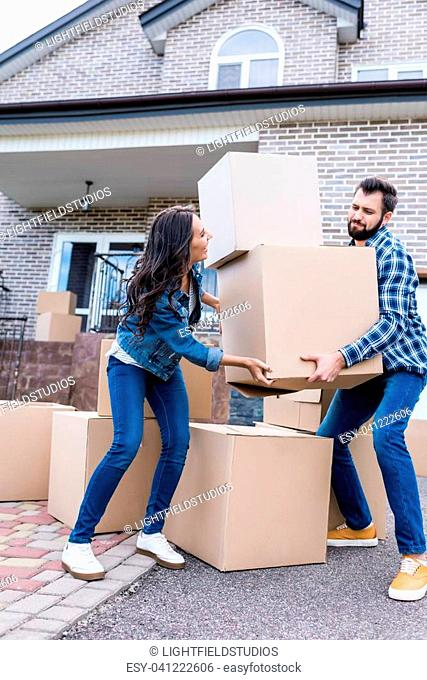 beautiful couple with boxes moving into new house together