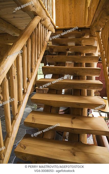 Wooden stairs leading to the master bedroom on the upstairs floor inside a handcrafted spruce log home, Quebec, Canada. This image is property released