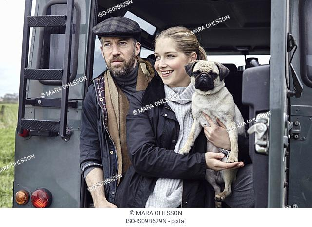 Country couple with dog looking out from back door of off road vehicle