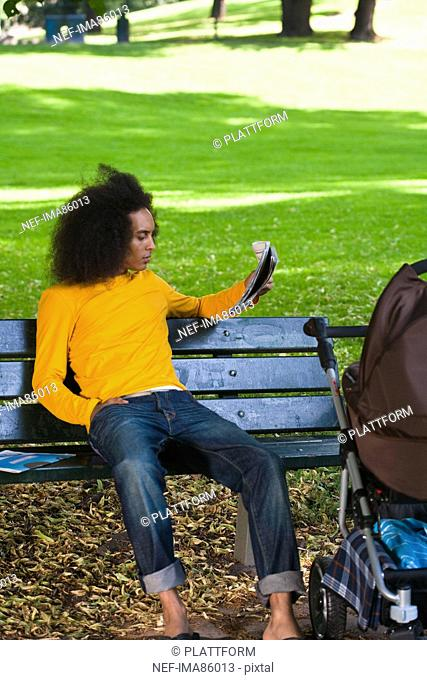 Young man with baby carriage sitting on bench and reading newspaper