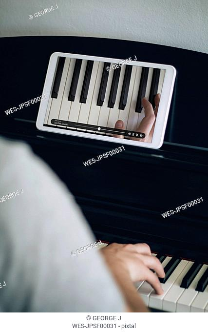 Man learning playing piano with video tutorial on a tablet
