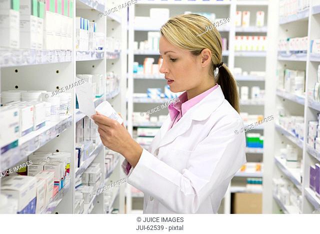 Pharmacist reading prescription and bottle in pharmacy