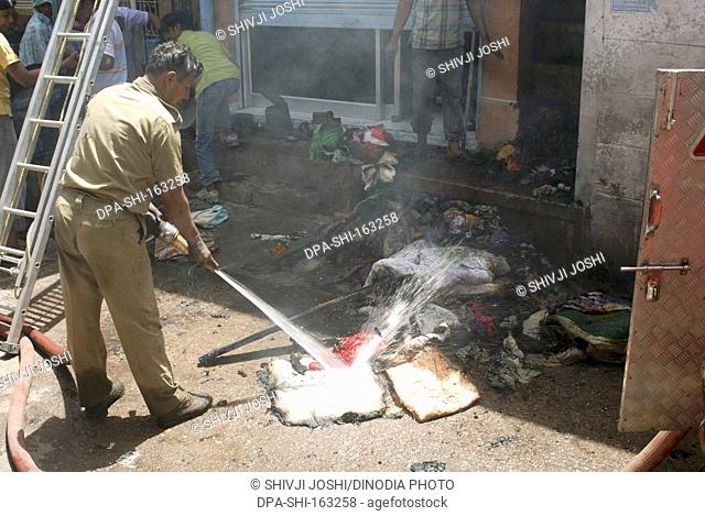 Fire Brigade worker spraying water on burnt goods of fire victim house in lane ; Jodhpur ; Rajasthan ; India