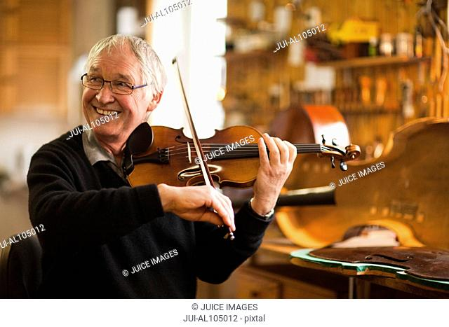Senior violin maker testing violin