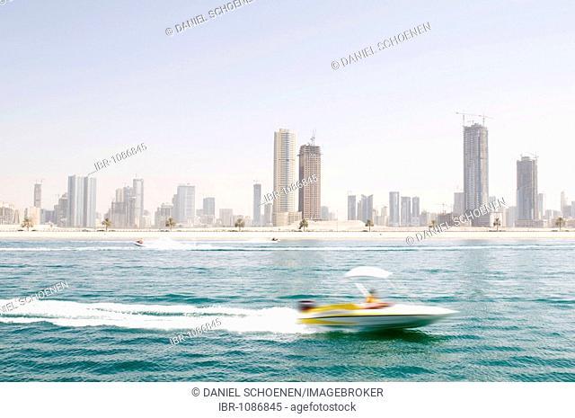 Skyline of Sharjah with speedboat, blurred, Dubai, United Arab Emirates