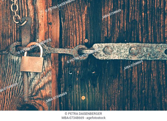 A wooden door is secured with a latch and a padlock