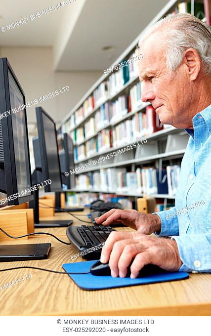 Senior man working on computer in library