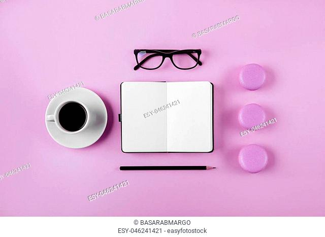 Coffee, macaron, clean notebook, eyeglasses and flower on violet table from above. Female working desk. Flat lay style