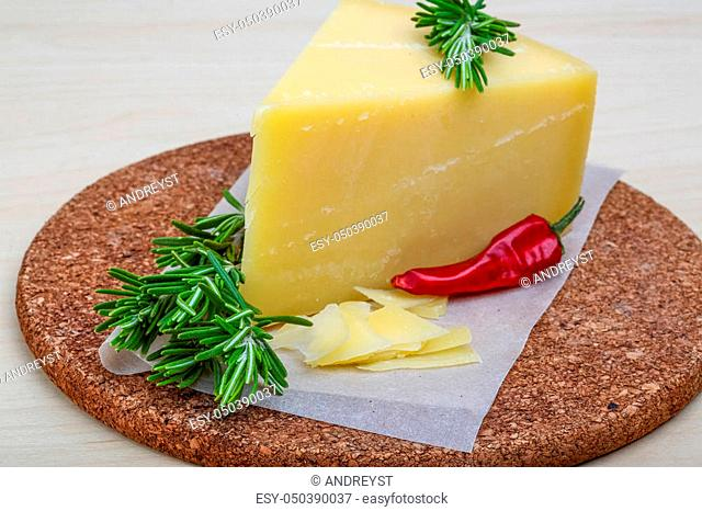 Parmesan cheese with rosemary on the wood background