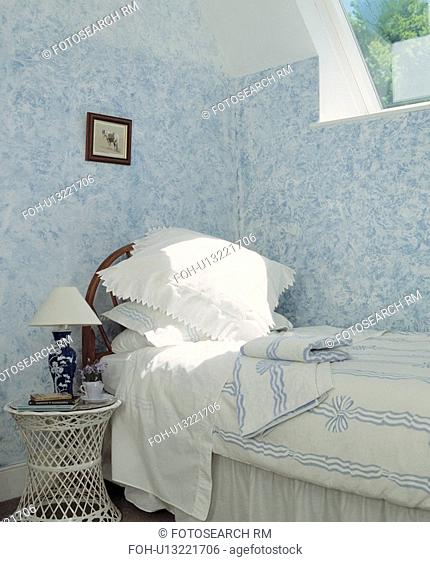 White pillows and blue+white duvet on bed below window in bedroom with painted stippled blue+white walls