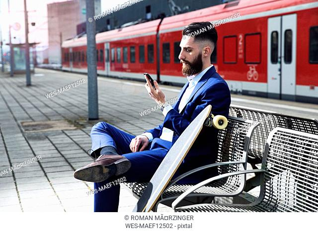 Young man with longboard sitting at train station, using smartphone