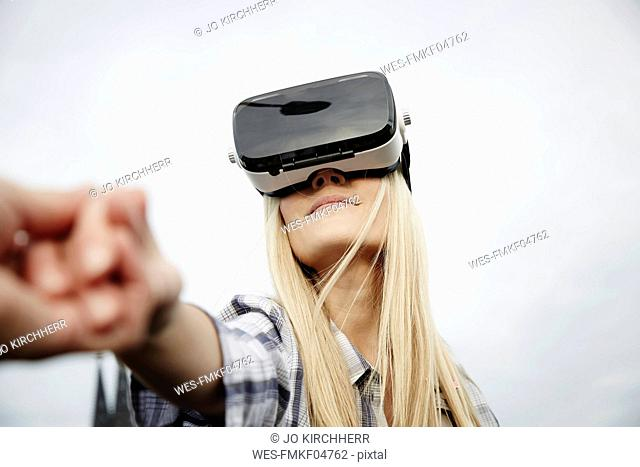 Woman wearing Virtual Reality Glasses holding hands