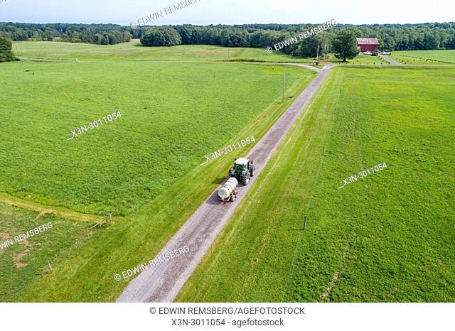 Tractor hauling liquid tank down farm lane in Mercer County Pennsylvania, USA