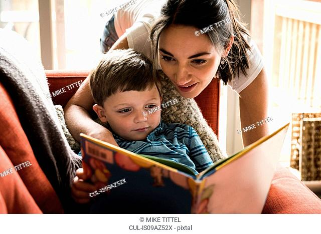 Mother teaching son to read book on sofa