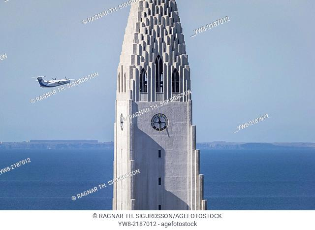 Twin Engine turboprop known as The de Havilland Canada Dash 8-300, flying close to the tower of Hallgrimskirkja Church, Reykjavik, Iceland