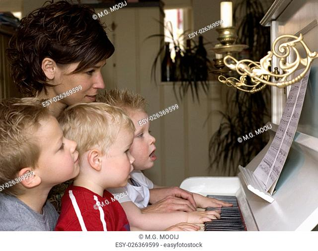A cute family picture were four people are playing the piano