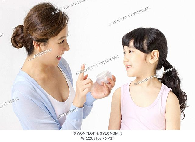 Mother holding a facial cream to apply on her daughter's face both looking at each other with a smile