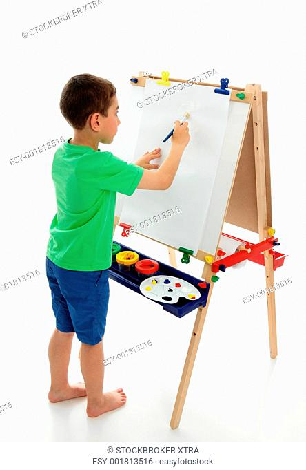 A little boy starting to paint a picture using acrylic paints and art paper on an easel. White background