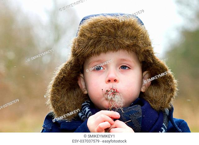 young boy blowing seeds on a cold winters day