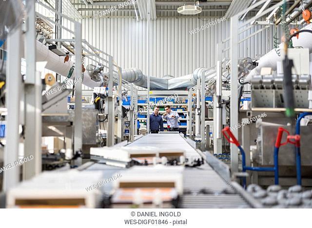 Two men talking at conveyor belt in factory shop floor