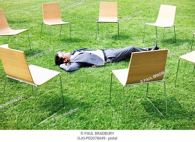Businessman laying in grass surrounded by chairs