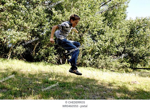 Side profile of a boy jumping in a park