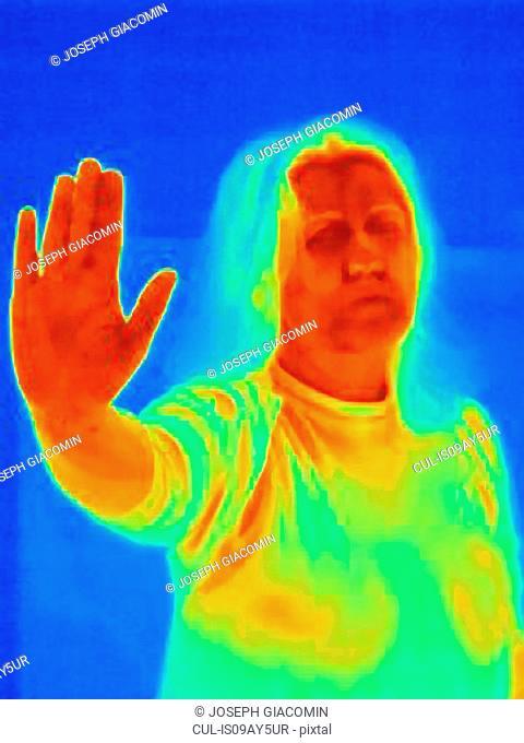 Thermal image of woman raising hand in stop gesture