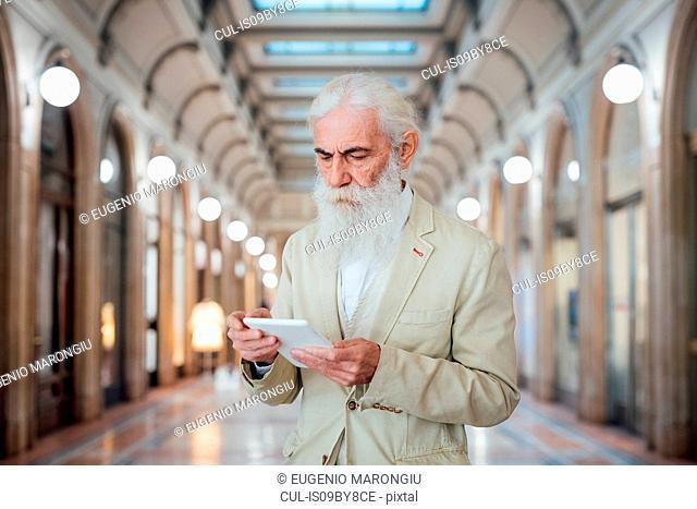 Senior businessman using digital tablet inside office building, Milano, Lombardia, Italy