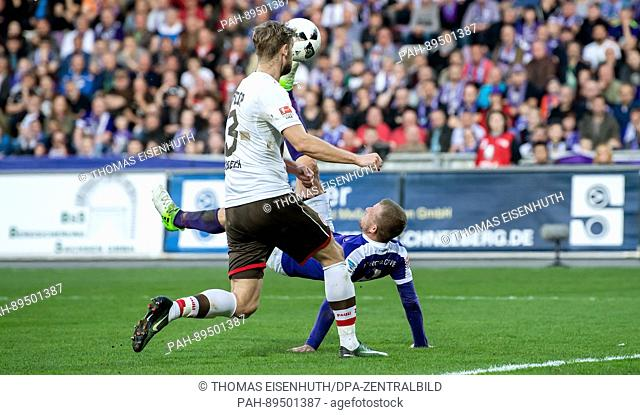 Aue's Nicky Adler (middle) scores a 1:0 goal with a bicycle kick against St. Pauli's Lasse Sobiech during the bundesliga soccer match between FCErzgebirge Aue...