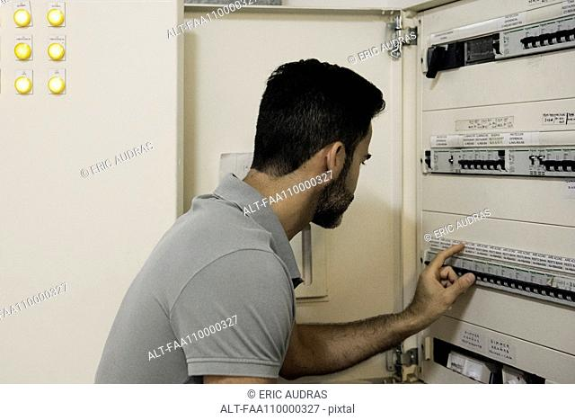 Electrician checking electric control cabinet