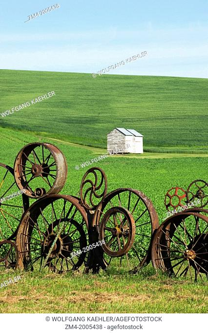USA, WASHINGTON STATE, PALOUSE, UNIONTOWN, FENCE MADE OUT OF OLD WHEELS AT DAHMEN BARN ART GALLERY
