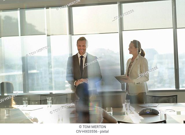 Smiling businessman leading conference room meeting