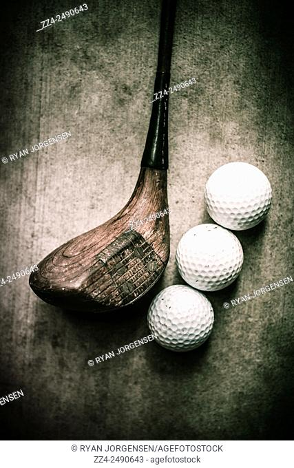 Traditional wooden golf club with balls on grunge cement surface. Art of golfing