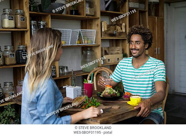 Smiling couple enjoying a meal together in cozy restaurant