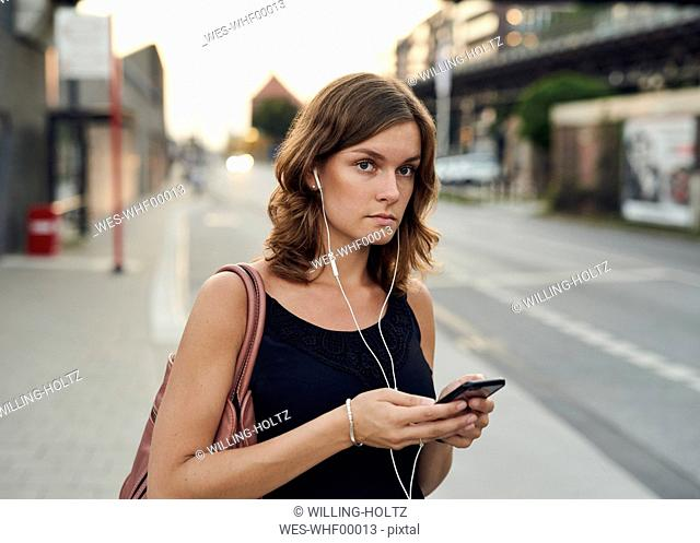 Germany, Young woman with smart phone exploring Hamburg