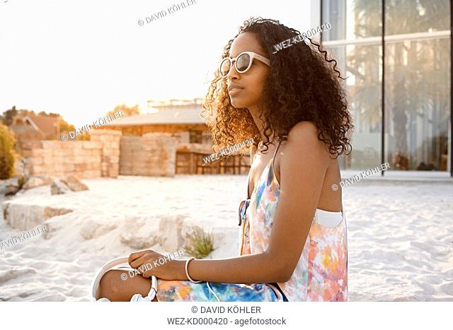 Young woman with headphones and sunglasses on beach