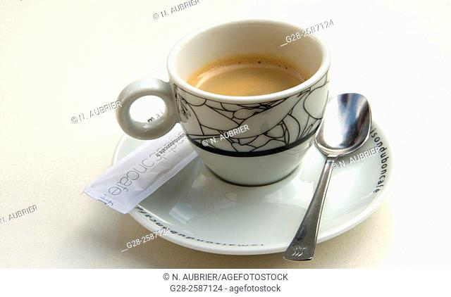 China cup full of coffee on a cafe table, with castor sugar and teaspoon, symbol of coffee break or danger of diabetes