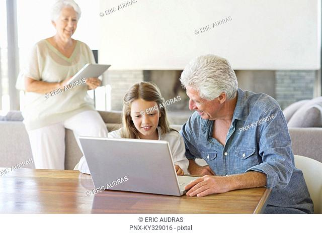 Man using a laptop with his granddaughter and his wife working on a digital tablet in background