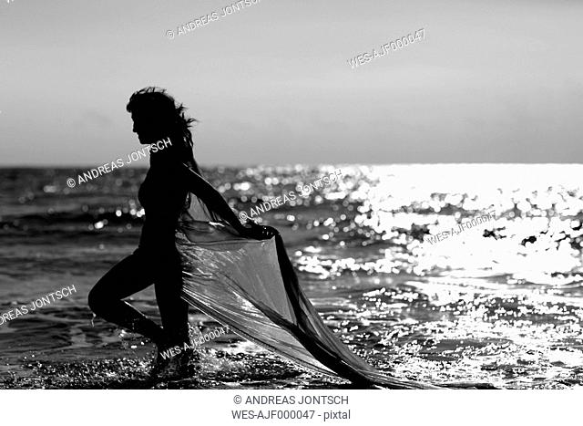 Silhouette of young woman walking at the sea