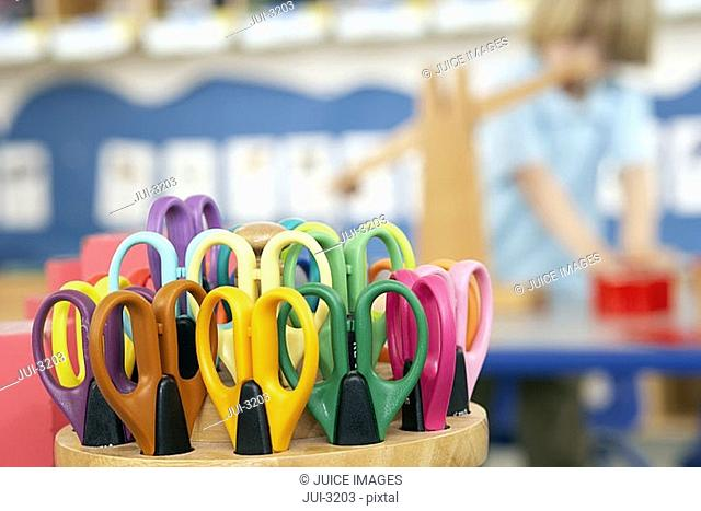 Boy 4-6 standing in classroom, focus on multi-coloured scissors in pot in foreground