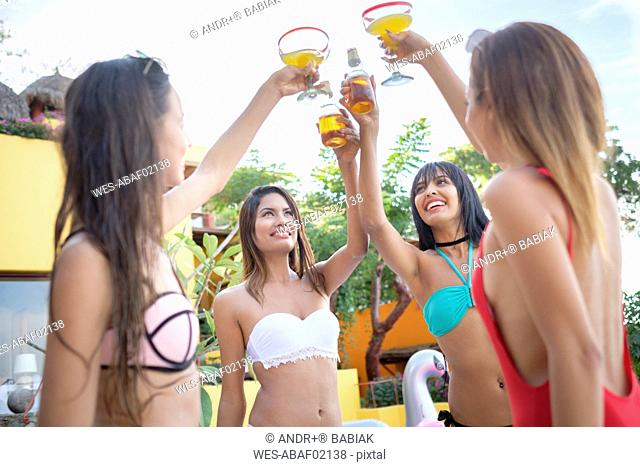 Four young women clinking cocktail glasses and beer bottles in a resort