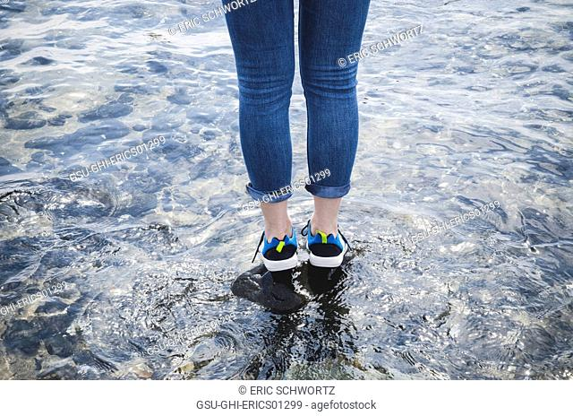 Young Woman Wearing Water Shoes Standing on Rock, Canon Beach, Oregon, USA