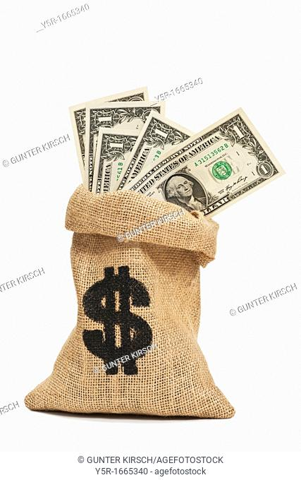 Many U S Dollar bills with the portrait of George Washington are in a jute bag