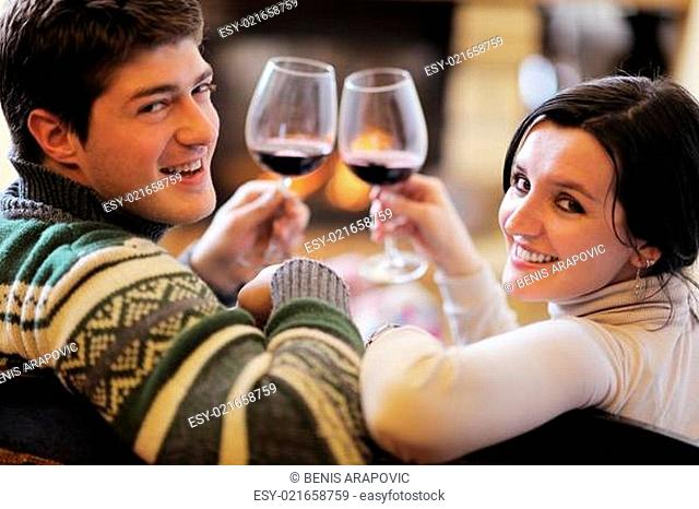 Young romantic couple sitting on sofa in front of fireplace at h