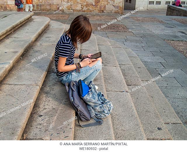 A teenage woman with a tablet on the stairs of a university in a university campus