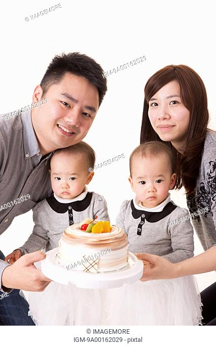 Young family with baby twins celebrating birthday together