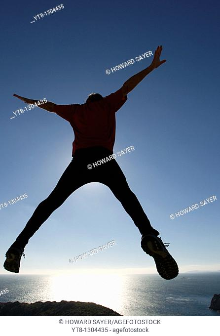 Man leaping through the air by the sea