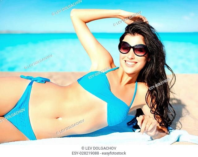 travel, tourism, summer holidays, vacation and people concept - happy beautiful woman in bikini and shades sunbathing over exotic tropical beach background
