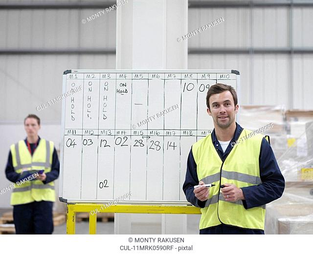 Workers With Whiteboard In Warehouse